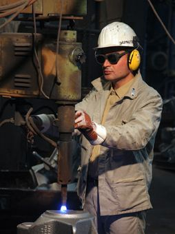 Worker wearing a helmet with ear protection, goggles and gloves